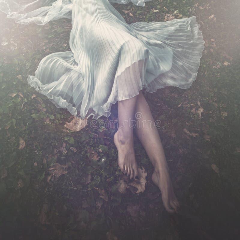 Bugia scalza della donna su erba nel giorno di estate del corpo più basso del vestito elegante fotografie stock libere da diritti