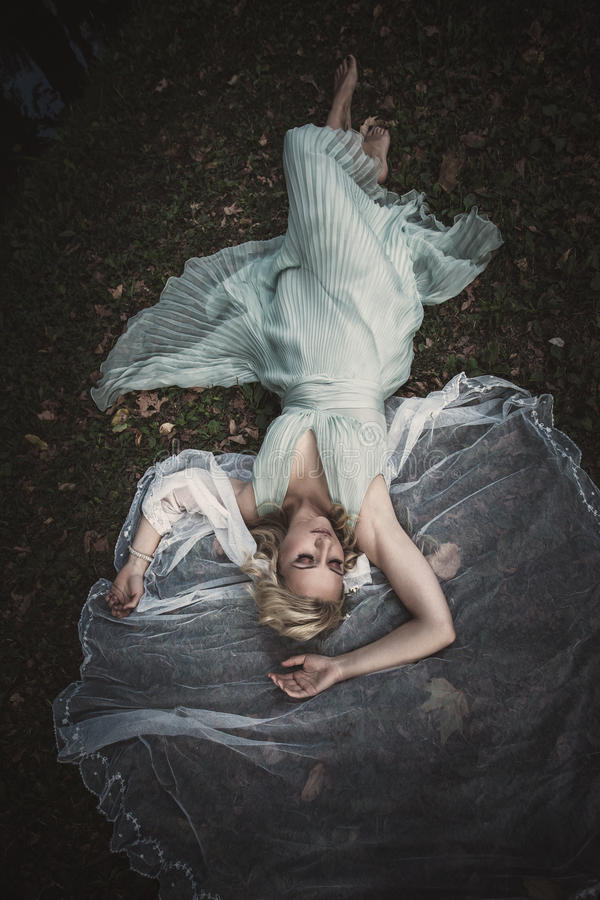 Bugia scalza della sposa sui gras e sulle foglie con il velo intorno lei immagini stock