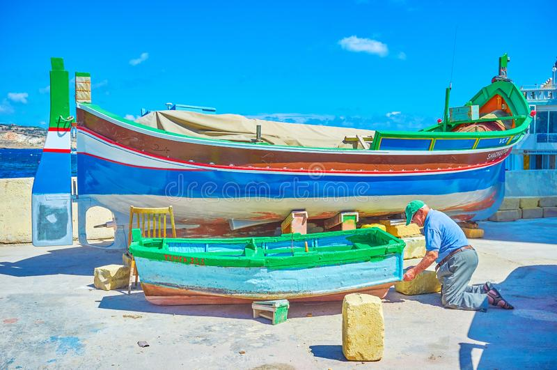 The senior boatman. BUGIBBA, MALTA - JUNE 14, 2018: The senior boatman repairs and paints the old wooden dinghy on the shore of fishing harbour, on June 14 in royalty free stock photography