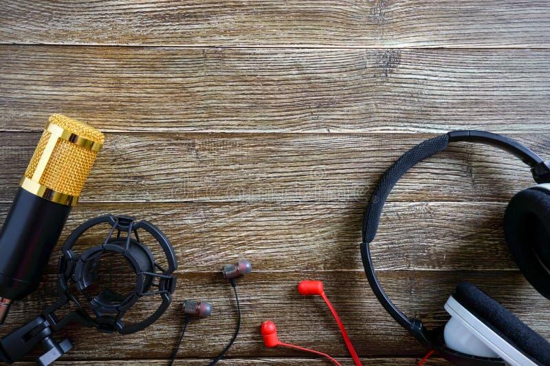 Bugie del microfono e delle cuffie dell'oro del condensatore su una tavola di legno con lo spazio della copia Tema musicale immagine stock libera da diritti