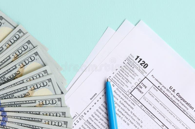1120 bugie della forma di imposta vicino a cento banconote in dollari ed alla penna blu su un fondo blu-chiaro Dichiarazione dei  immagine stock