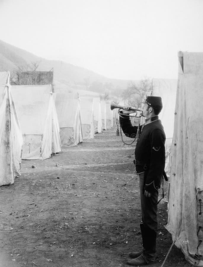 Bugle de soufflement de soldat dans le camp d'armée (toutes les personnes représentées ne sont pas plus long vivantes et aucun do photographie stock libre de droits