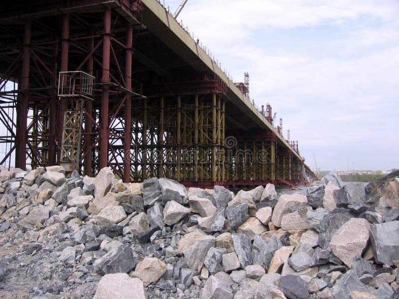 Bugrinskij för konstruktion för  för Ñ-Ñ€ÑƒÑ  Ñ bro i Novosibirsk på floden Ob en hög av stora stenar för byggnadskonstruktion arkivbild