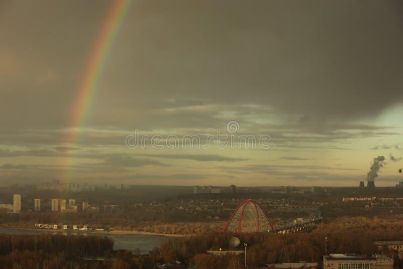 Bugrinskybrug over de Ob-rivier in Novosibirsk tegen bewolkte hemel met een heldere regenboog stock foto's