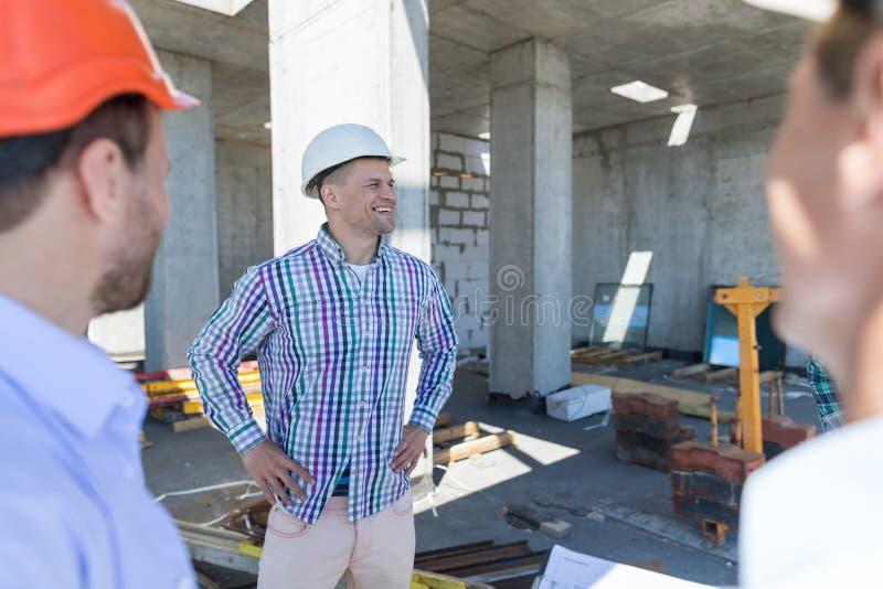 Buiders auf Baustelle, Leute-errichtendes Geschäfts-Konzept führt Gruppe aus stockbild