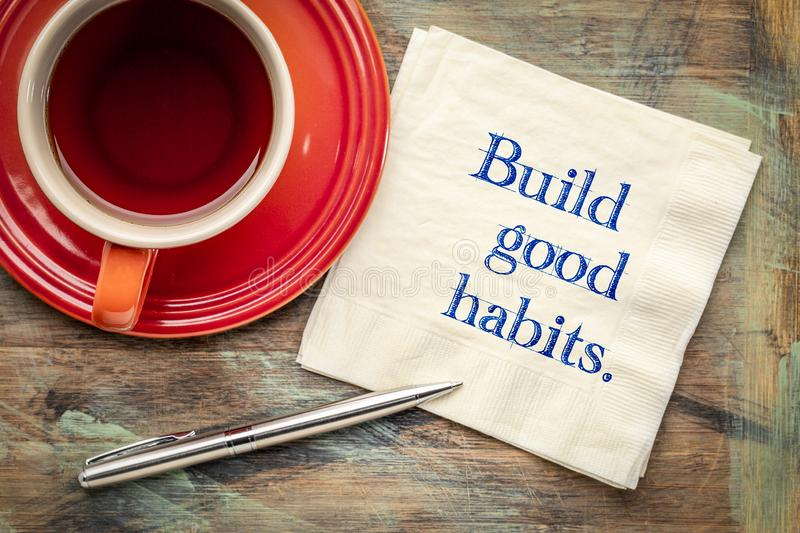Build good habits - note on napkin. Build good habits - inspirational handwriting on a napkin with a cup of tea stock photo