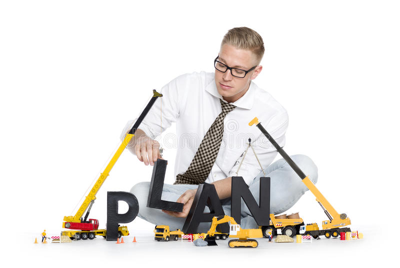 Build up a plan: Businessman building plan-word. royalty free stock image