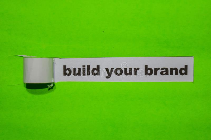Build Your Brand, Inspiration and business concept on green torn paper stock image
