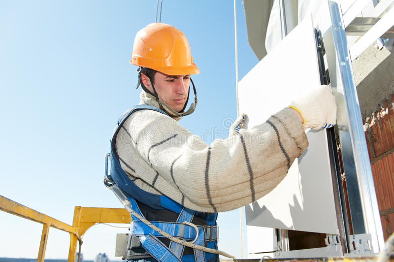 Builder at aerated facade tile installation. Worker builderinstalling big tile on aerated facade constructiona of building royalty free stock images
