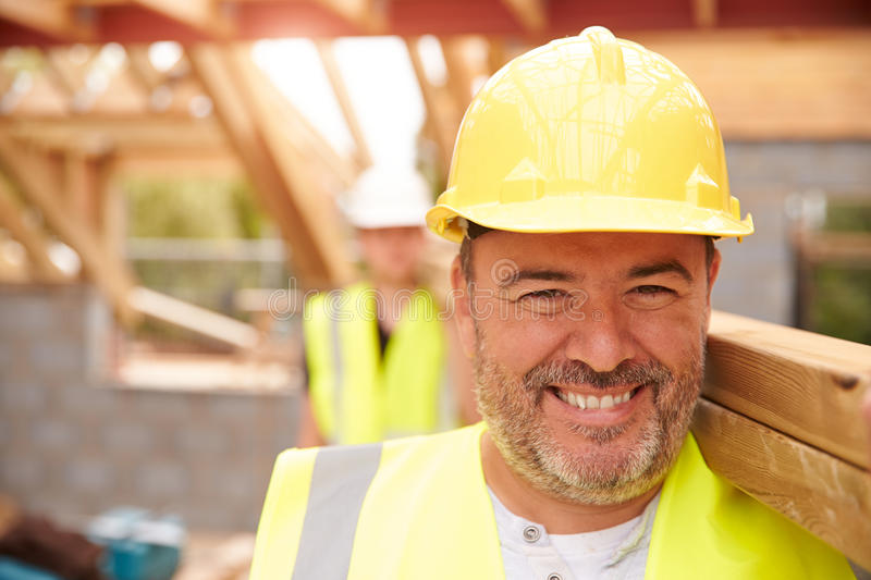 Builder And Apprentice Carrying Wood On Construction Site royalty free stock images