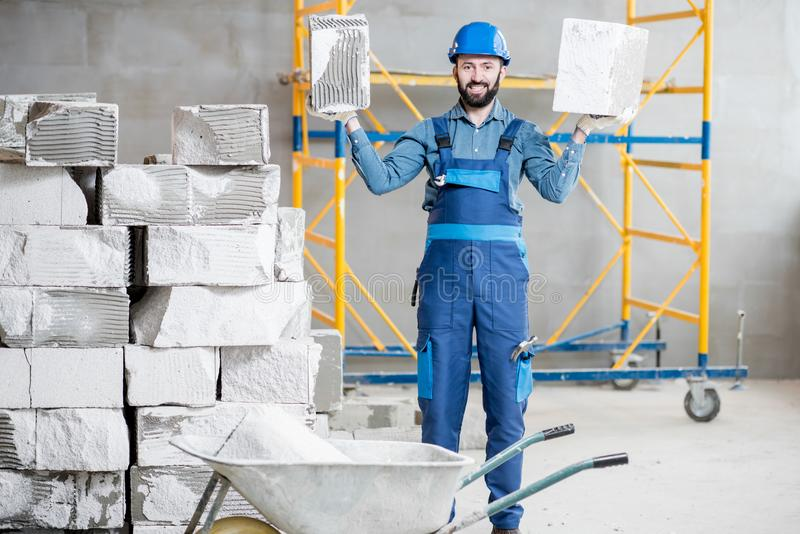 Builder with blocks indoors. Portrait of a strong builder in uniform holding blocks at the construction site indoors royalty free stock images