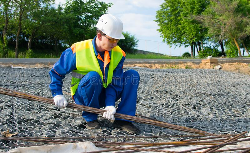 The Builder in a blue uniform and a white helmet, against stones, takes long metal rods for construction of reinforced concrete royalty free stock photo