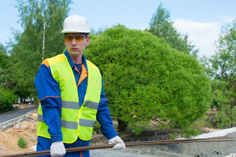 The Builder in a blue uniform and a white helmet, carries reinforcement for the formwork of the Foundation royalty free stock images