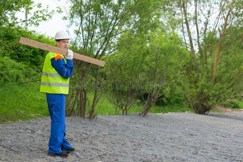 Builder in a blue uniform and white helmet, carries a wooden beam on a stone embankment royalty free stock photo