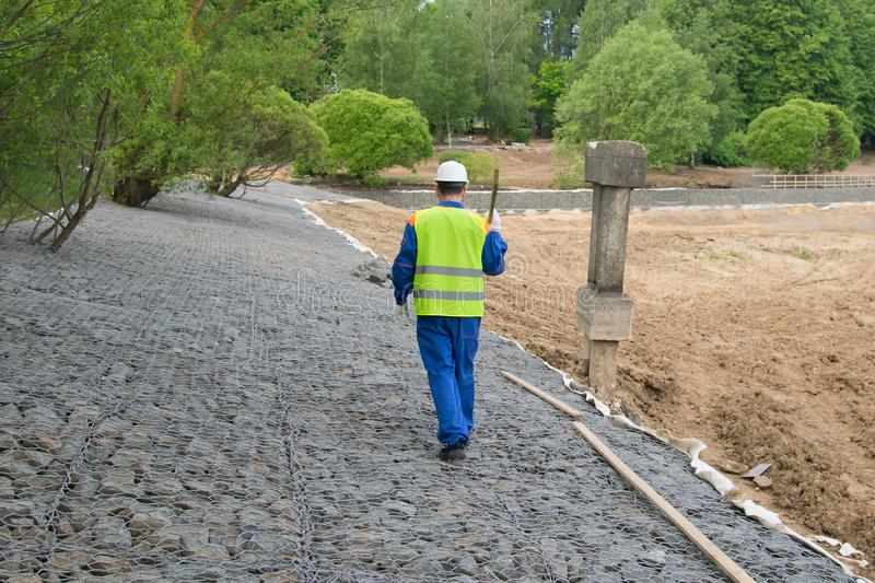 A builder in a blue uniform and a white helmet, carries a wooden beam on a stone embankment, the rear view, there is space for royalty free stock image