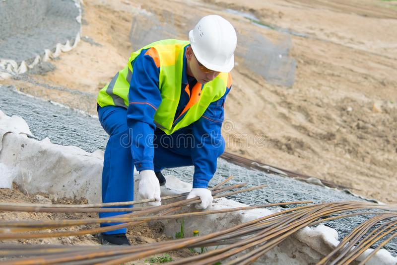 Builder in blue uniform and white helmet, takes to carry the reinforcement for the Foundation, close-up stock photos