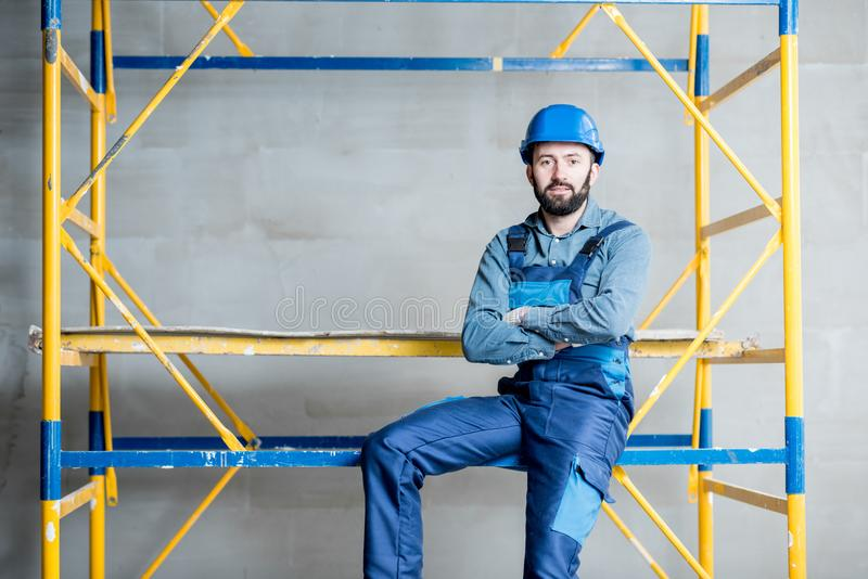 Builder on the scaffolding indoors. Builder in blue working uniform sitting on the scaffolding indoors stock photos
