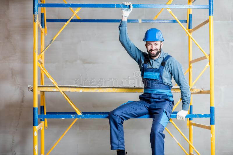 Builder on the scaffolding indoors. Builder in blue working uniform sitting on the scaffolding indoors royalty free stock photos