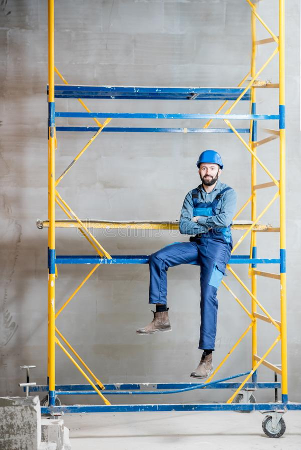 Builder on the scaffolding indoors. Builder in blue working uniform sitting on the scaffolding indoors royalty free stock image