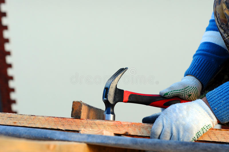Builder Building Roof. Worker Hammer in Nails on the Roof. Roofer Hammering a Nail into the new Roof Beams. Construction Nails stock photography