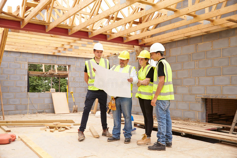 Builder On Building Site Looking At Plans With Apprentices stock images