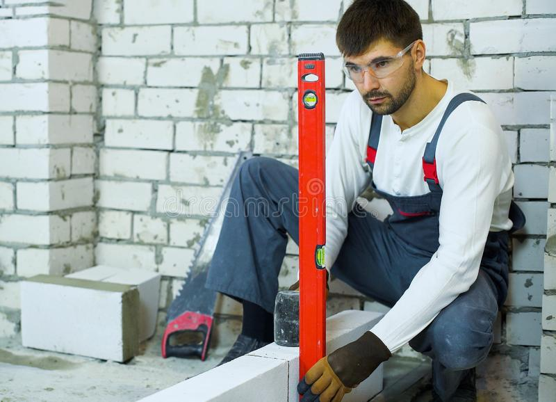 Builder checking evenness of aerated concrete wall with bubble level. Builder checks evenness of aerated concrete wall with bubble level. construction worker in royalty free stock photography