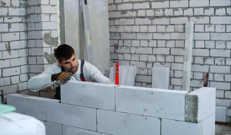 Builder checking evenness of aerated concrete wall with spirit level. Builder checks evenness of aerated concrete wall with spirit level. construction worker in stock image