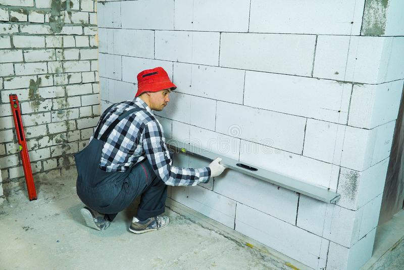 Builder checking quality of aerated concrete block wall with construction ruler. Worker in uniform pressing bubble level ruler to interior wall. construction royalty free stock images