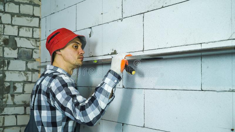 Builder checking straightness of aerated concrete block wall with bubble level. Young man pressing construction ruler to interior wall. construction, building royalty free stock image