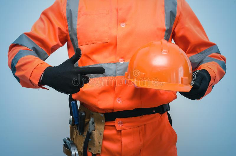 Builder. Worker. Repairman. Builder construction worker holding in hand a hard hat and is showing on it by his index finger. Safety instruction on construction royalty free stock image