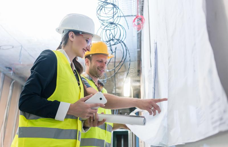 Builder and construction worker looking at building blueprint royalty free stock image