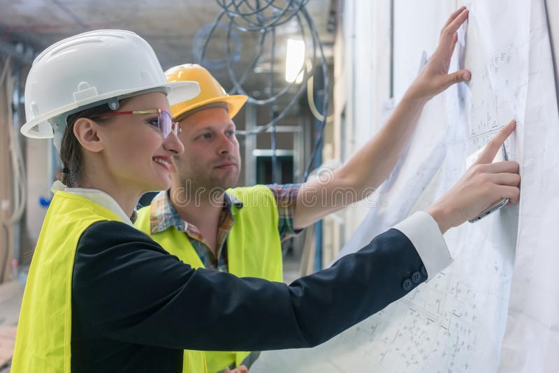 Builder and construction worker looking at building blueprint royalty free stock images