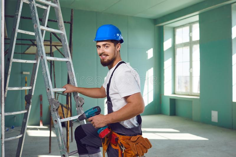 Builder contractor bearded man in helmet smiling while standing at a construction site. royalty free stock photography