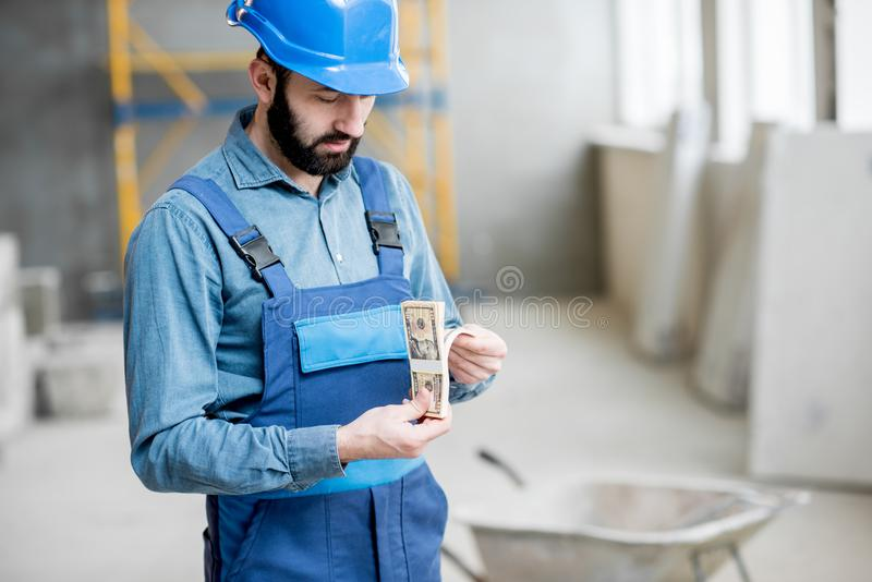 Builder with salary at the construction site stock photos