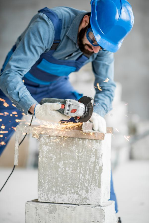 Builder cutting metal indoors. Builder in working uniform cutting metal profile with cutting machine at the construction site indoors stock photography