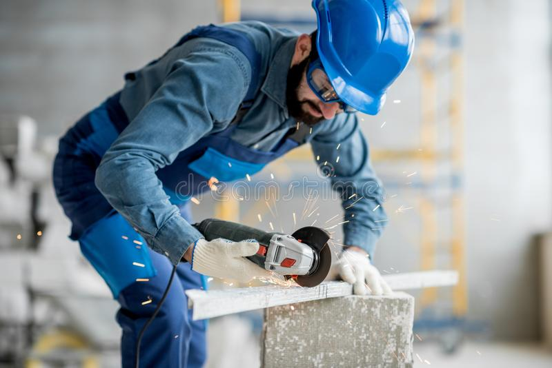 Builder cutting metal indoors. Builder in working uniform cutting metal profile with cutting machine at the construction site indoors stock images