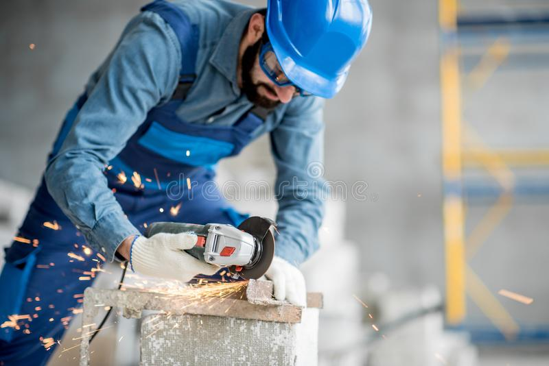 Builder cutting metal indoors. Builder in working uniform cutting metal profile with cutting machine at the construction site indoors stock image