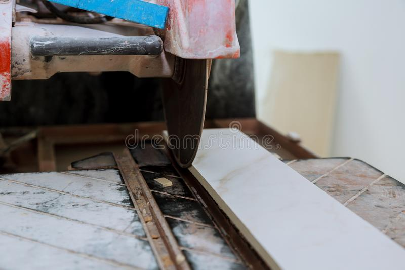 Builder in cutting tiles with big electro saw on the construction stock photos