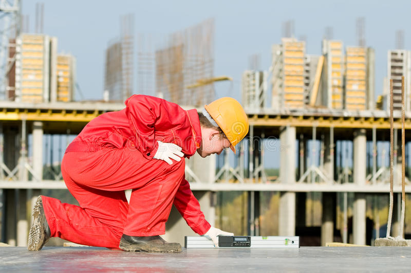 Builder with digital level royalty free stock photo