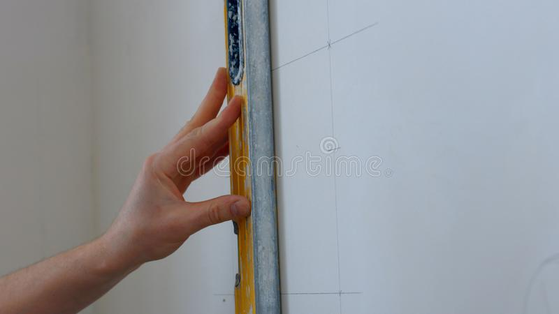 Builder draws marking on the wall. stock photos