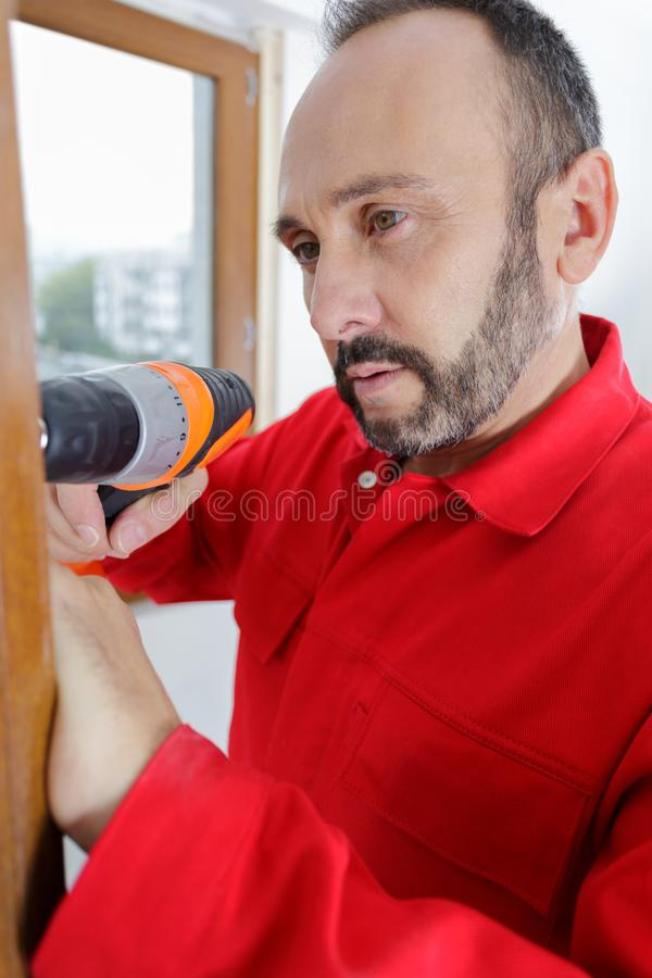 Builder with drill inserting door frame to aperture royalty free stock photos