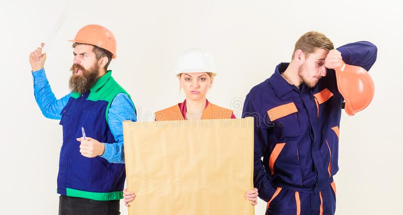 Builder, engineer, architect argue at work. Disagreement concept. Men and woman in helmets, architects on confused expression with drawing, plan, blueprint royalty free stock photos