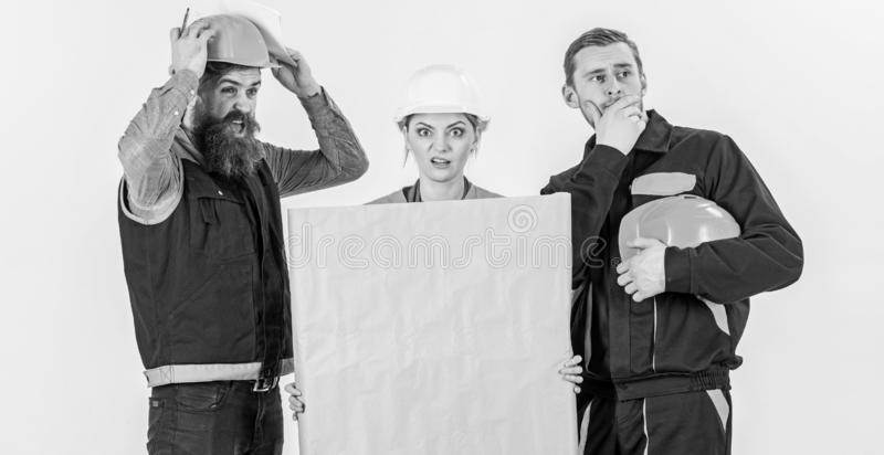Builder, engineer, architect confuse at work. Confusing concept. Men and women in helmets, architects on confused expression with drawing, plan, blueprint royalty free stock image