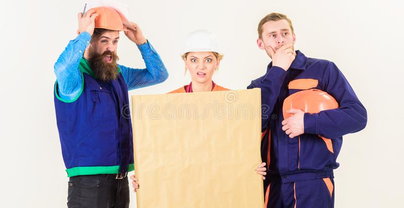 Builder, engineer, architect confuse at work. Confusing concept. Men and women in helmets, architects on confused expression with drawing, plan, blueprint stock images