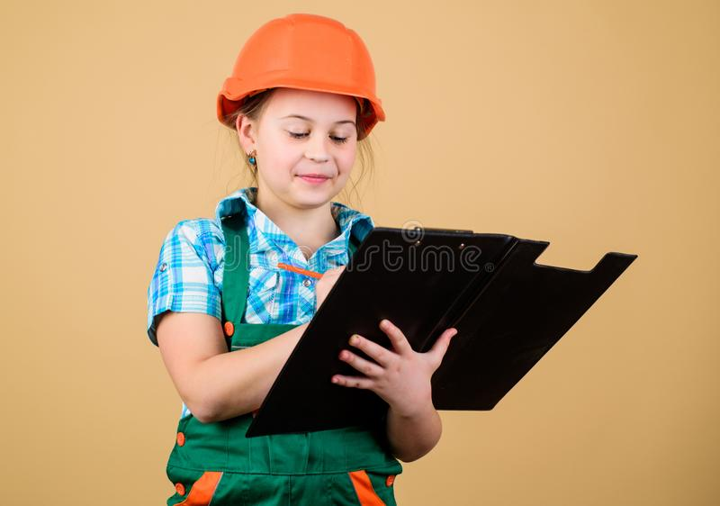 Builder engineer architect. Kid worker in hard hat. Child care development. small girl repairing in workshop. Foreman. Inspector. Repair. Safety expert. Future stock photo