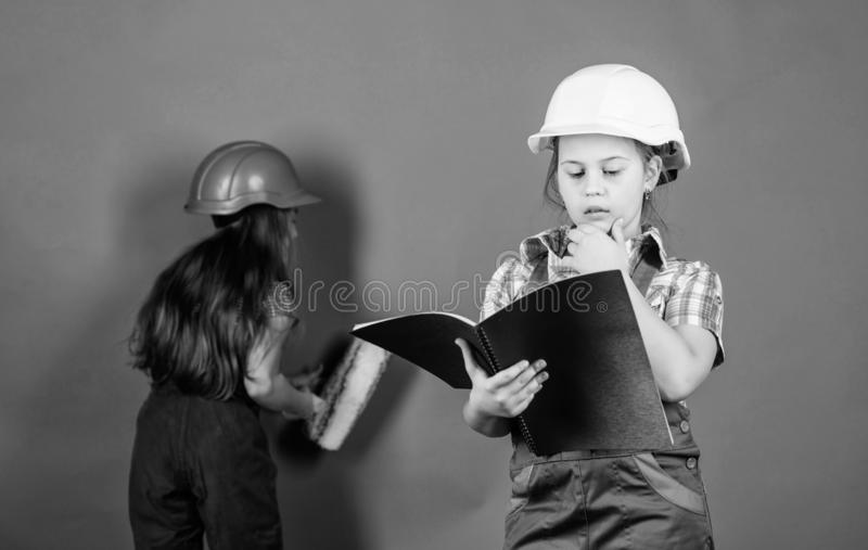Builder engineer architect. Kid worker in hard hat. Child care development. small girls repairing together in workshop. Tools to improve yourself. Repair royalty free stock photography