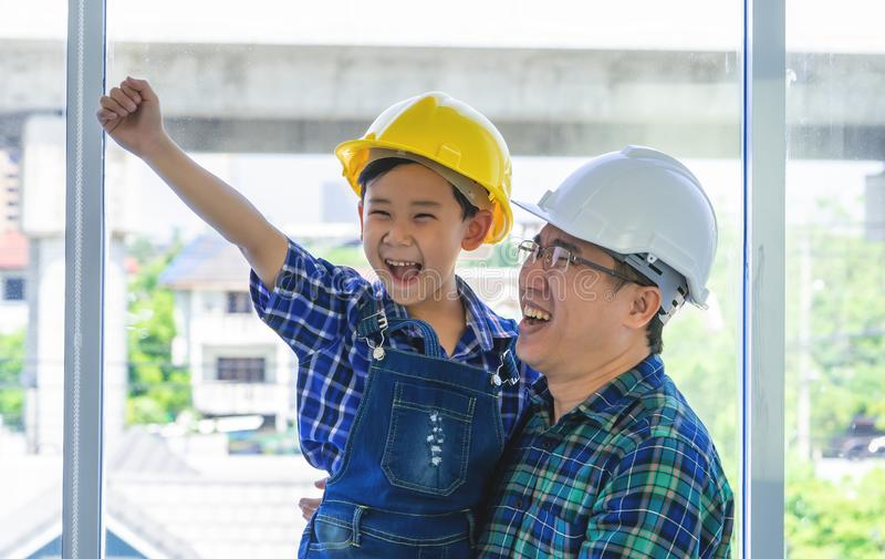 Builder Father holding son with engineering protecting hat for father day success concept. Builder Father holding his son with engineering protecting hat for royalty free stock image