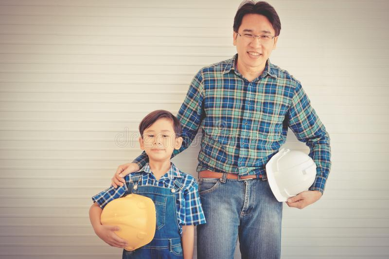 Builder father Standing next to his son for family connection concept in vintage tone, For Family bonding and fatherhood love. Builder father is Stading next to royalty free stock photography