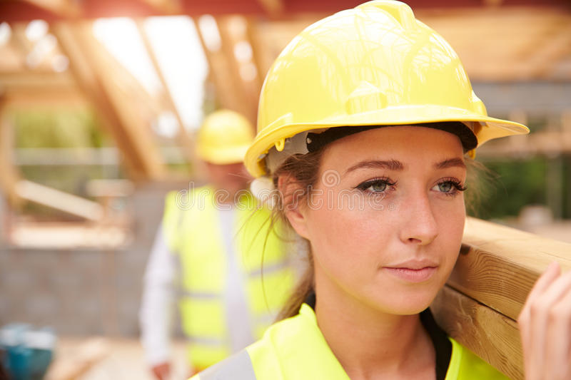 Builder And Female Apprentice Carrying Wood On Site stock image