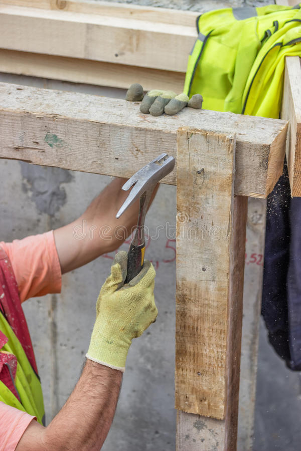 Builder hands hammering a nail into a plank 4 royalty free stock photos
